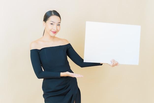 Bella giovane donna asiatica del ritratto con il tabellone per le affissioni bianco vuoto su yellow