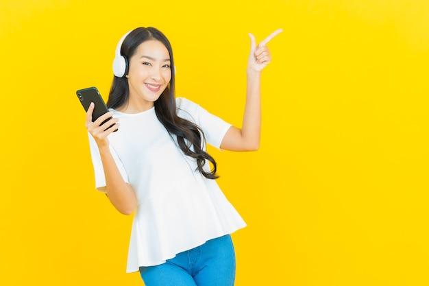 Ritratto bella giovane donna asiatica con cuffie e smartphone per ascoltare musica su giallo