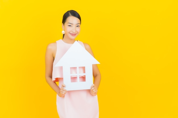 Bella giovane donna asiatica del ritratto con il segno di carta della casa o della casa su colore giallo