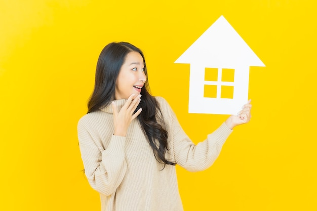 Bella giovane donna asiatica del ritratto con il segno della carta della casa sulla parete gialla