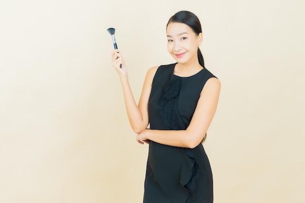 Bella giovane donna asiatica del ritratto con il cosmetico della spazzola di trucco sulla parete di colore