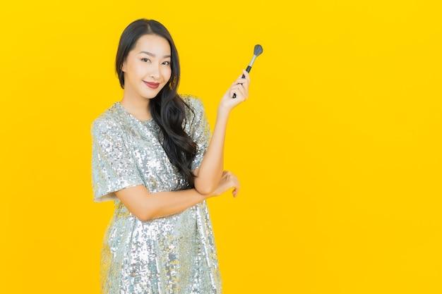 La bella giovane donna asiatica del ritratto con compone il cosmetico della spazzola su giallo