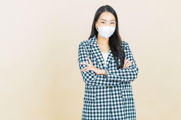 Ritratto bella giovane donna asiatica con maschera per proteggere covid19 o virus su giallo
