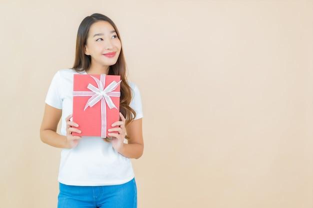 Bella giovane donna asiatica del ritratto con il contenitore di regalo rosso sul beige