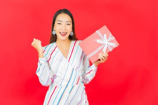 Bella giovane donna asiatica del ritratto con il contenitore di regalo rosso