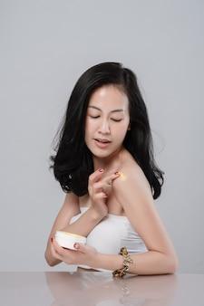 Ritratto di bella giovane donna asiatica avvolta in un asciugamano che spande la crema sulla sua spalla.