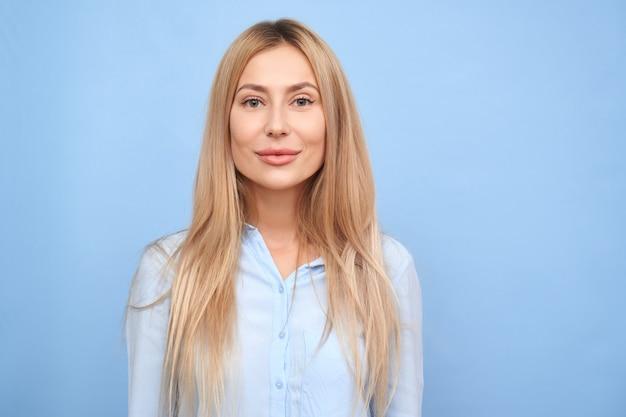 Bella giovane donna bionda del ritratto in camicia di affari che sorride ed esamina la macchina fotografica isolata sulla parete blu con lo spazio della copia