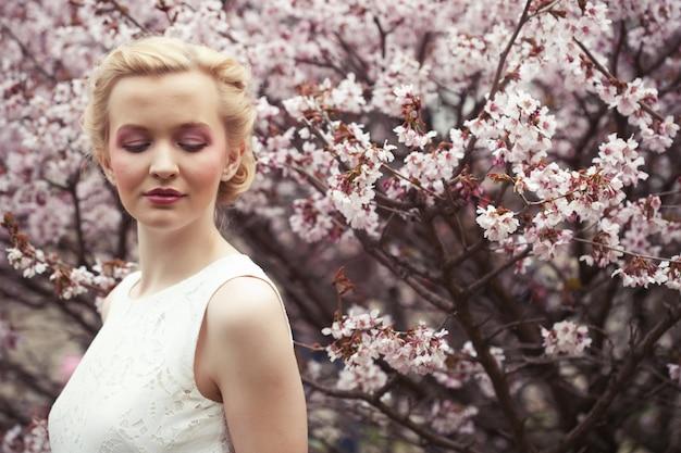 Ritratto di una giovane e bella donna bionda su uno dei fiori di ciliegio rosa in primavera