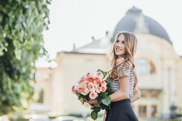 Ritratto di una bellissima giovane donna bionda in piedi con un mazzo di rose