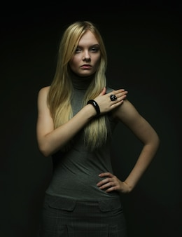 Ritratto di bella ragazza bionda nel buio. foto di moda.