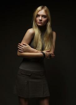 Ritratto di bella ragazza bionda sopra la parete scura. foto di moda.