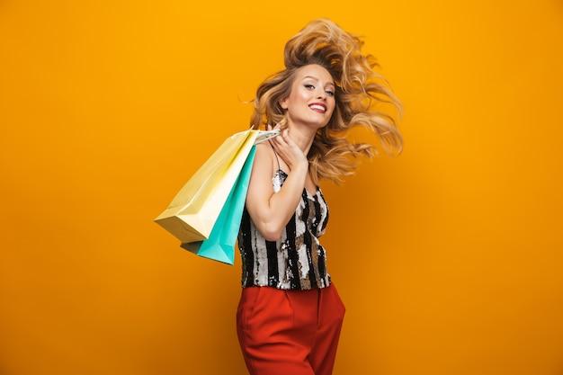 Ritratto di una giovane e bella donna bionda in piedi isolato su sfondo giallo, portando le borse della spesa
