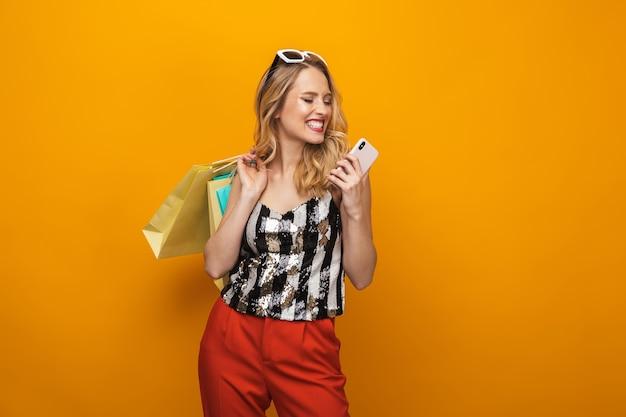 Ritratto di una giovane e bella donna bionda in piedi isolato su sfondo giallo, utilizzando il telefono cellulare
