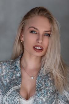 Ritratto di una bellissima giovane donna bionda con trucco naturale con gli occhi azzurri con labbra sexy in una camicia vintage con un motivo in studio contro un muro grigio