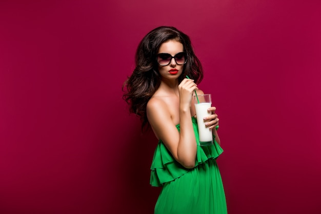 Ritratto di bella giovane bruna in occhiali da sole e verde dre