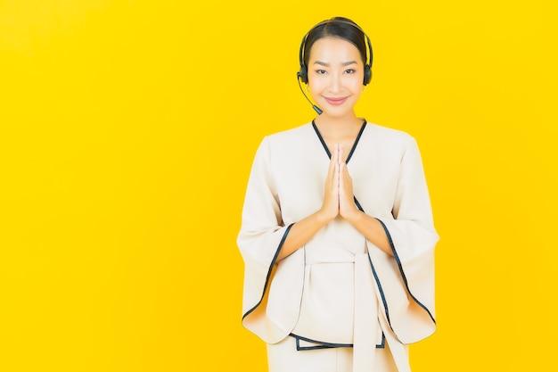Ritratto di bella giovane donna asiatica di affari con l'auricolare per l'assistenza clienti del call center sulla parete gialla