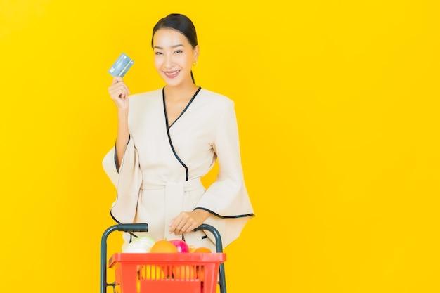 Ritratto di bella giovane donna asiatica di affari con la drogheria del cestino della spesa dal supermercato sulla parete gialla