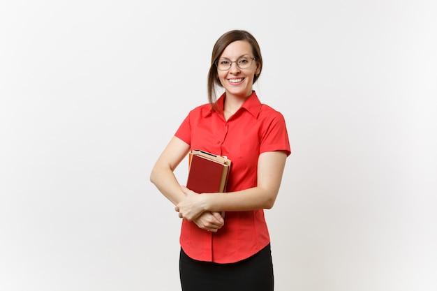 Ritratto di bella giovane donna dell'insegnante di affari in camicia rossa, gonna nera e vetri che tengono i libri in mani isolate su fondo bianco. istruzione o insegnamento nel concetto di università delle scuole superiori
