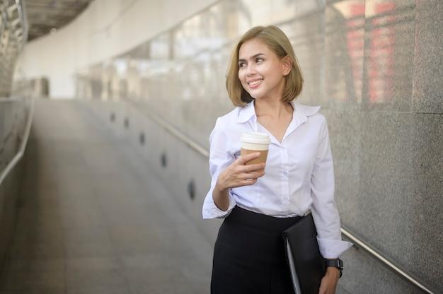 Ritratto di bella giovane donna d'affari caucasica sta lavorando nella città moderna
