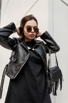 Ritratto di una bella giovane donna fresca con occhiali da sole rotondi vintage in abiti neri alla moda: giacca di pelle rock e felpa con una borsa alla moda passeggiate in città. stile femminile urbano