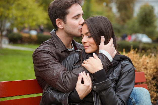 Ritratto di una bella giovane coppia che abbraccia all'aperto sulla panchina