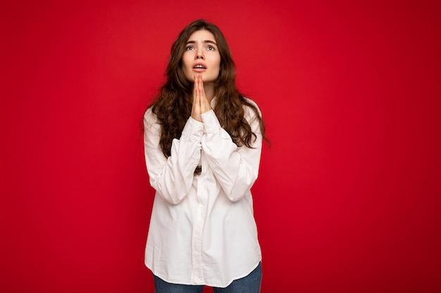 Ritratto di bella giovane donna castana riccia che porta camicia bianca isolata su fondo rosso con