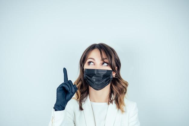 Ritratto di una bella e giovane dottoressa in abito medico bianco, guanti di gomma neri e maschera nera sul dito del viso rivolto verso l'alto su uno sfondo bianco copyspace