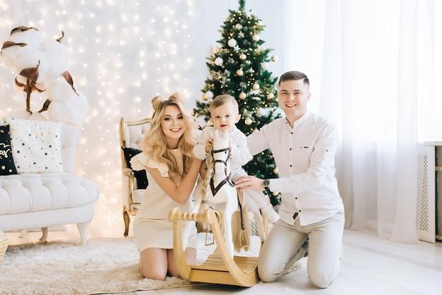 Ritratto di una giovane e bella famiglia sullo sfondo dell'albero di natale