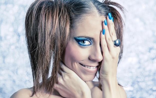 Ritratto di una bellissima modella con le trecce, un trucco brillante e una manicure blu su uno sfondo metallico sfocato blurred