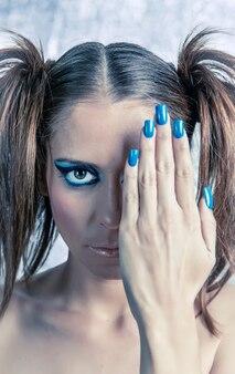 Ritratto di una bellissima modella con le trecce, un trucco brillante e una manicure blu su uno sfondo metallico sfocato