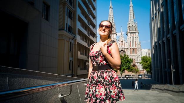 Ritratto di bella ragazza in abito corto che cammina nella città vecchia con edifici antichi e moderni. visita turistica femminile della città europea