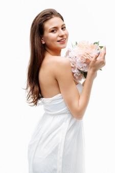 Ritratto bella ragazza sorridente e in posa con fiori artificiali sul muro bianco in abito bianco in