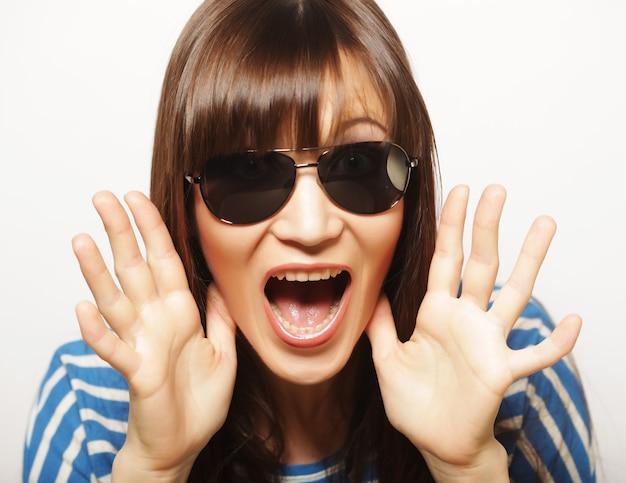 Ritratto di bella ragazza in occhiali da sole uno sguardo di sorpresa
