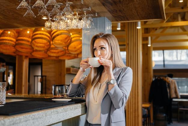 Ritratto di una bella ragazza che beve un caffè delizioso in un bellissimo caffè moderno