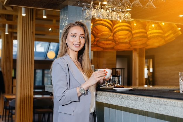 Ritratto di una bella ragazza che beve un caffè delizioso in un bellissimo caffè moderno.