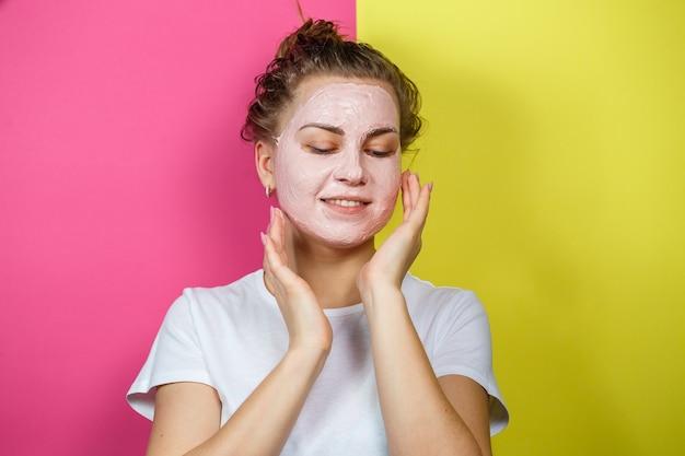 Ritratto di una bellissima ragazza che si mette una maschera rinfrescante sul viso per ringiovanire e tonificare la pelle. trattamenti di bellezza