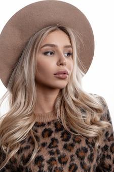 Ritratto di una bella ragazza con trucco naturale con labbra sexy con capelli biondi ricci lunghi in un cappello elegante in un maglione leopardato alla moda