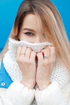 Ritratto di una bella giovane ragazza felice con gli occhi azzurri con un'elegante sciarpa lavorata a maglia e una giacca invernale bianca sul blu all'aperto