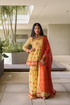 Ritratto di giovane e bella donna indiana che indossa abiti tradizionali all'aperto