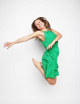 Ritratto di una bellissima giovane donna che salta di gioia su sfondo bianco