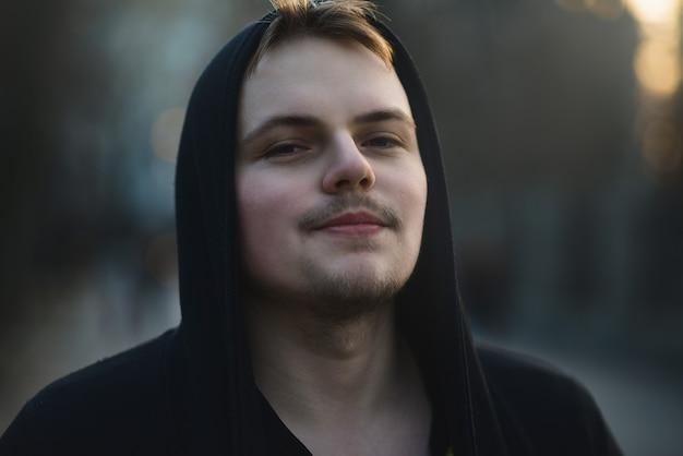Ritratto di bella giovane uomo che indossa la felpa con cappuccio