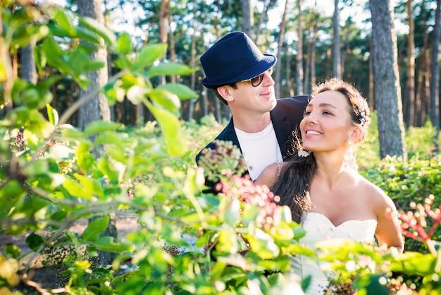 Ritratto di una giovane e bella coppia di sposi in posa in cespugli verdi sullo sfondo