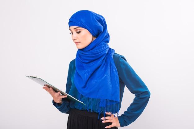 Ritratto di giovane e bella donna musulmana con cartella di file su sfondo bianco.