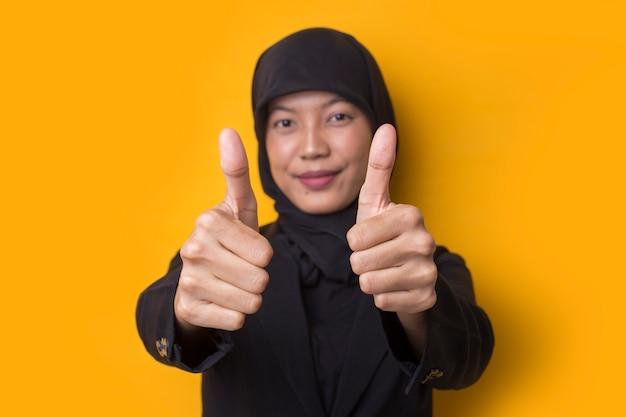Ritratto di una giovane e bella donna musulmana con i pollici in su