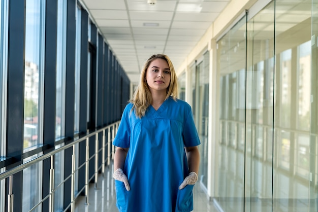 Ritratto di bella giovane infermiera in inofrm blu in clinica. assistenza sanitaria
