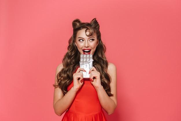 Ritratto di una giovane e bella ragazza pin-up che indossa un abito in piedi isolato, mangiando barretta di cioccolato