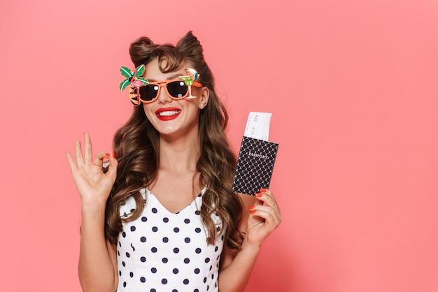 Ritratto di una giovane e bella ragazza pin-up che indossa un abito in piedi isolato, mostrando il passaporto con biglietto aereo