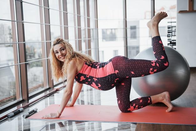 Ritratto di una giovane e bella donna incinta che tiene il suo stomaco seduto a esercizi presso il centro di formazione.