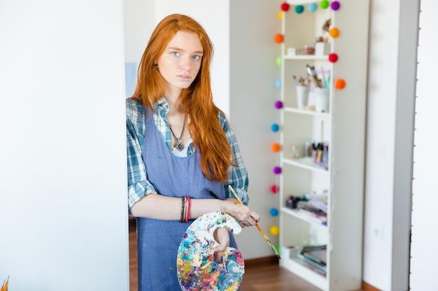 Ritratto di bella giovane pittrice rossa con tavolozza d'arte e pennello in officina d'arte