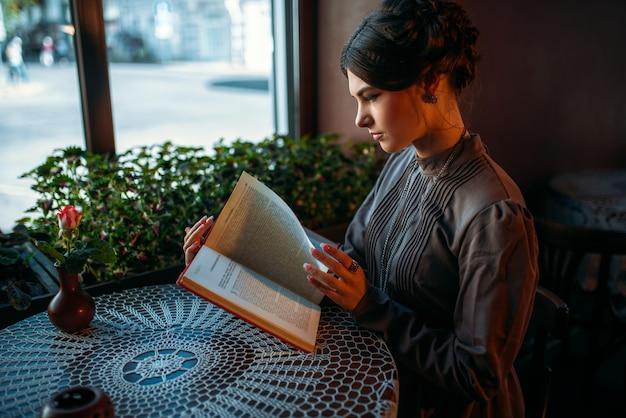 Ritratto di bella giovane signora retrò in caffè lettura libro vicino alla finestra.